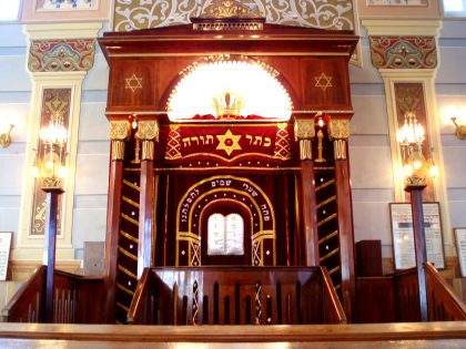 Interior of the Tbilisi synagogue with red curtains covering the Torah